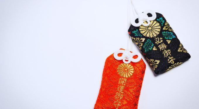 Zwei japanische Omamori in orange und schwarzGlücksbringer Anhänger