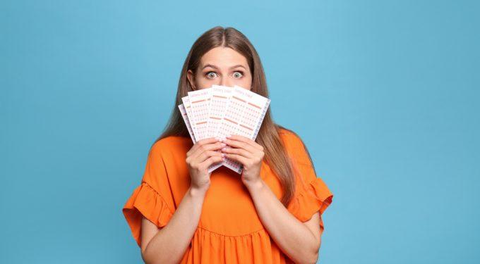 Frau mit aufgerissenen Augen hält Lottoscheine vor das Gesicht