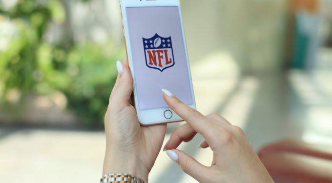 Frauenhand hält Iphone und ruft NFL bei Instagram auf