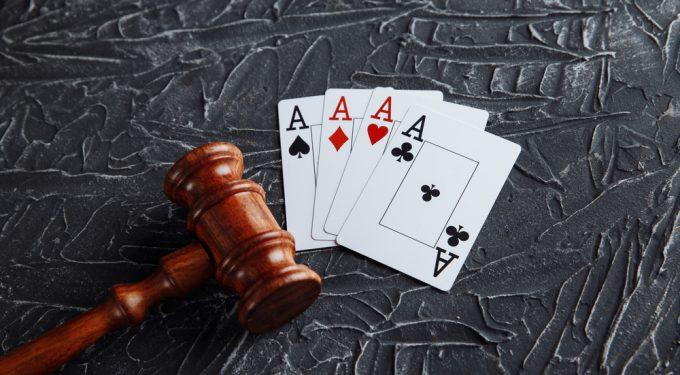 Vorteile legales Online Gluecksspiel_Richterlicher Hammer neben Spielkarten auf grauen Hintergrund