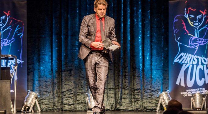 Mentalmagier Christoph Kuch auf der Bühne in festlichem Anzug