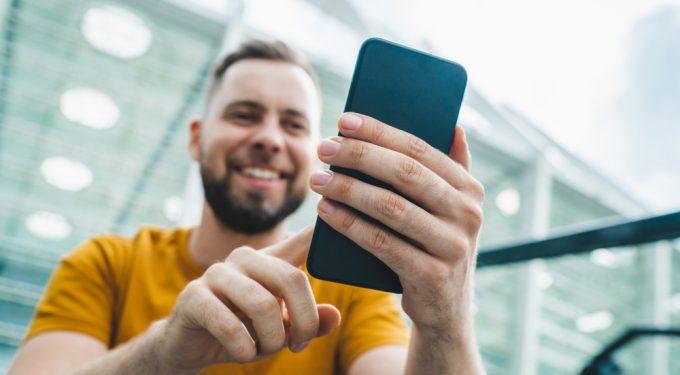 Mann mit Smartphone spielt Online Poker kostenlos
