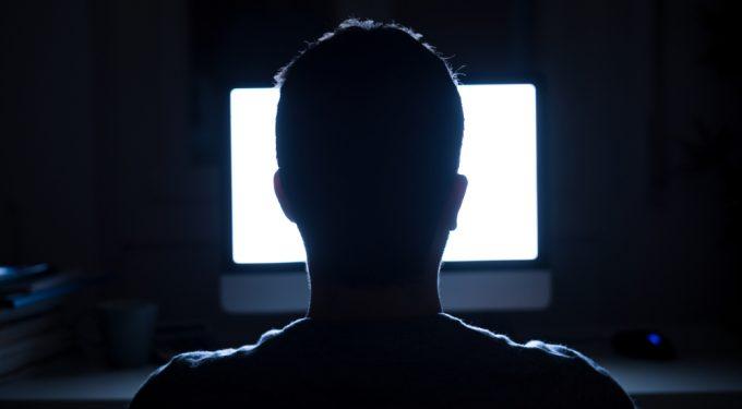 Mann von hinten vor Computer Bildschirm im dunklen Raum