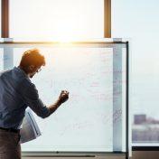 Unternehmer gibt Präsentation im Büro vor Whiteboard