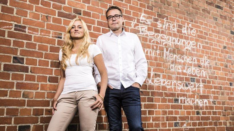 Steffen Moritz und seine Mitarbeiterin posieren vor einer Wand