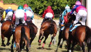 Pferde und Jockeys auf der Rennbahn