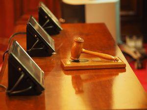 Gerichtssaal mit Hammer und Bildschirmen