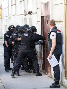 Beamte der Finanzpolizei brechen eine Tür auf