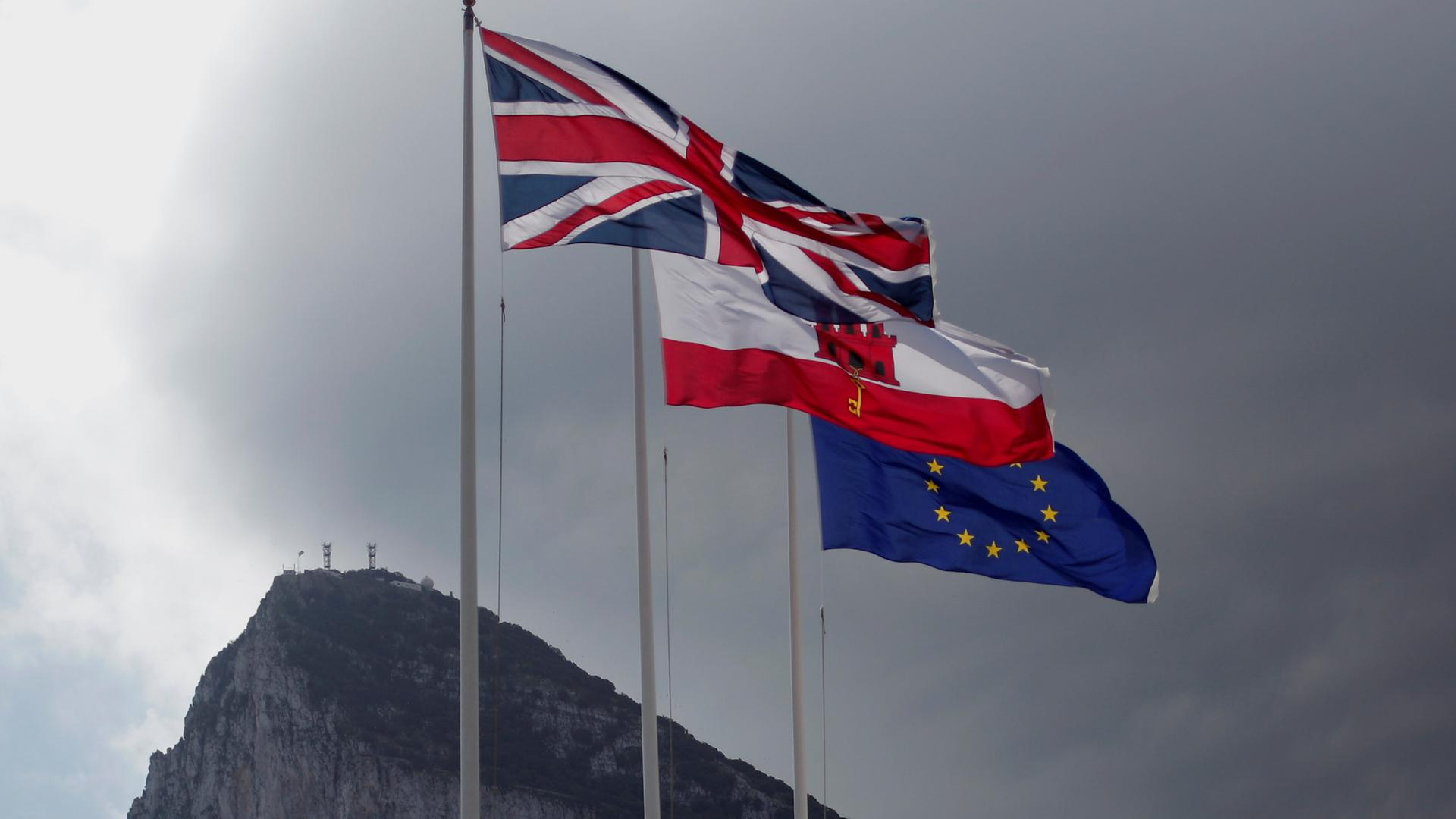 Drei Flaggen wehen auf Gibraltar, darunter die britische und die europäische.