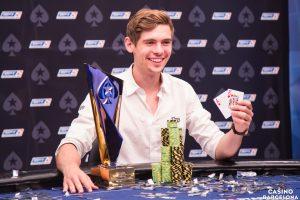 Fedor Holz posiert bei der EPT in Barcelona am Pokertisch mit der Starthand AK, seinem Pokal und seinem Chipstack
