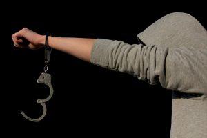 Jugendlicher mit Hoodie und Handschellen