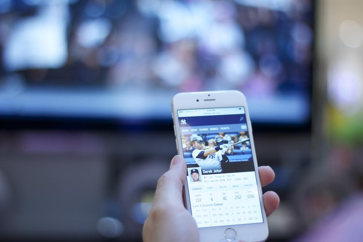 Smartphone in Hand Fernseher im Hintergrund