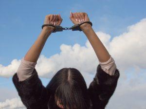Frau mit Handschellen Arme überm Kopf