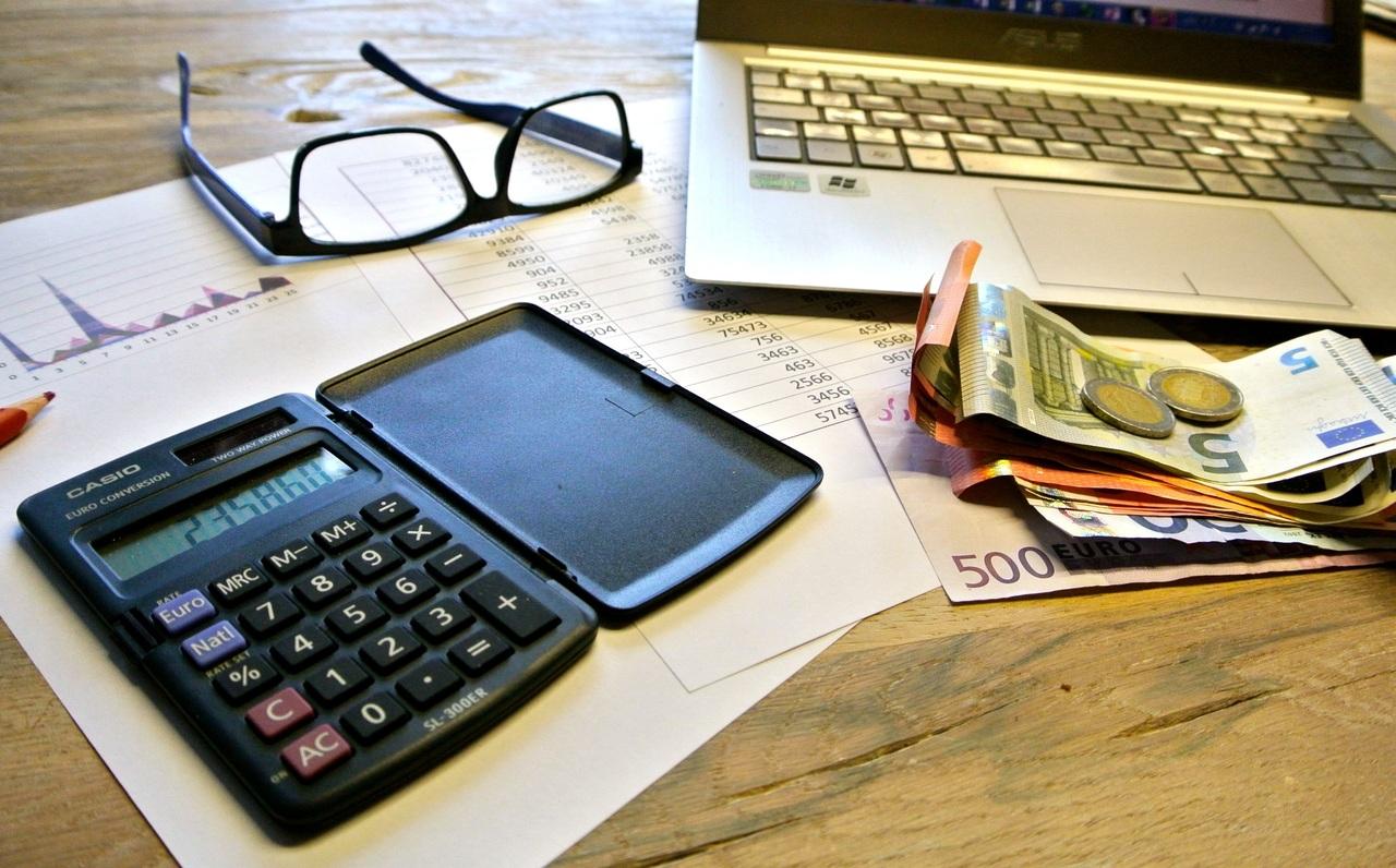 Ein Tisch mit Rechner und Geld