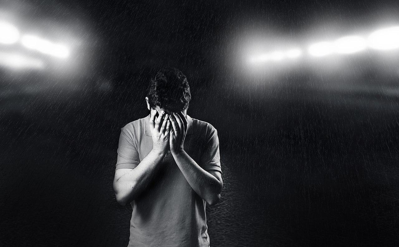 Verzweifelter Mann hält sich Hände vor Gesicht