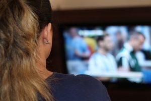 Frau vor Fernseher von hinten