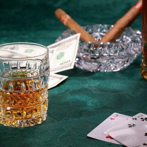 Whisky im Glas neben Spielkarten Geld und Zigarren