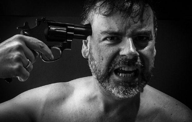Mann hält Pistole an Schläfe