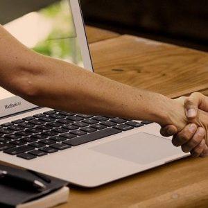 Zwei Hände schütteln sich durch einen Bildschirm