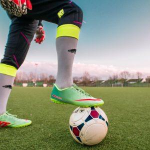 Fußballer stoppt Fußball mit Fuß auf dem Rasen