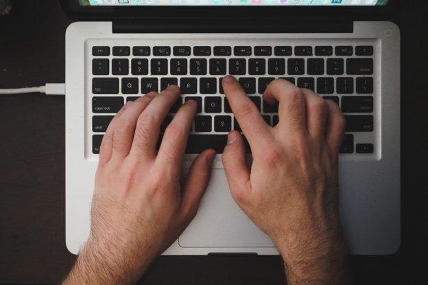 Person tippt mit zwei Händen auf Tastatur