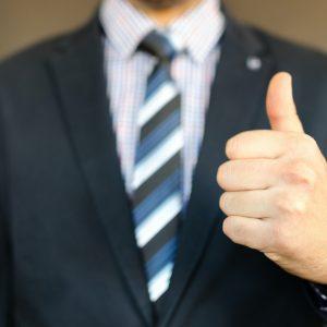 Mann im schwarzen Anzug, Krawatte, Daumen hoch