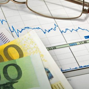 Geld, Brille und Stift auf Papier