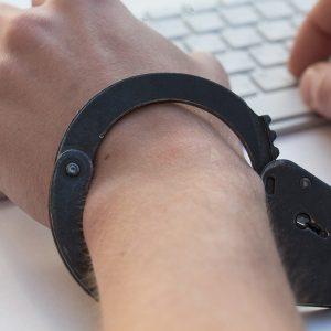 Person mit Handschellen am Computer