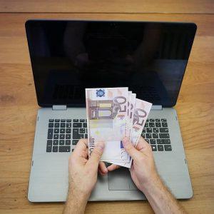 50 Euroscheine am Laptop Hände Geld