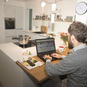 Mann am Laptop im Home-Office in der Küche