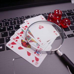Laptop, Spielkarten, Würfel, Lupe