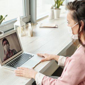 Frau am Laptop im Video-Anruf mit Schutzmaske