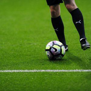 Fußballer mit Fußball auf Rasen