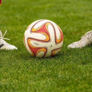Fußball auf Rasen zwei Spieler Füße Fußballschuhe