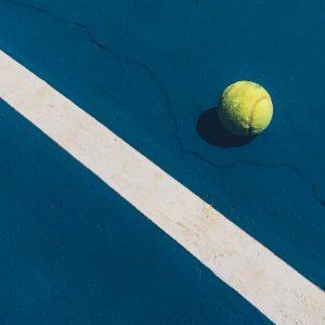 Tennisball auf blauem Platz