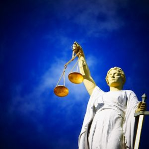 Justitia Statue unter blauem HImmel