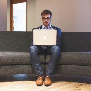 Mann am Laptop auf Sofa